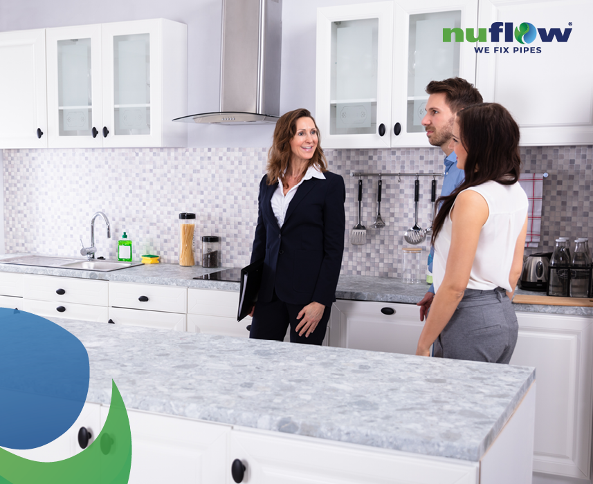 Real estate agent showing kitchen to young couple